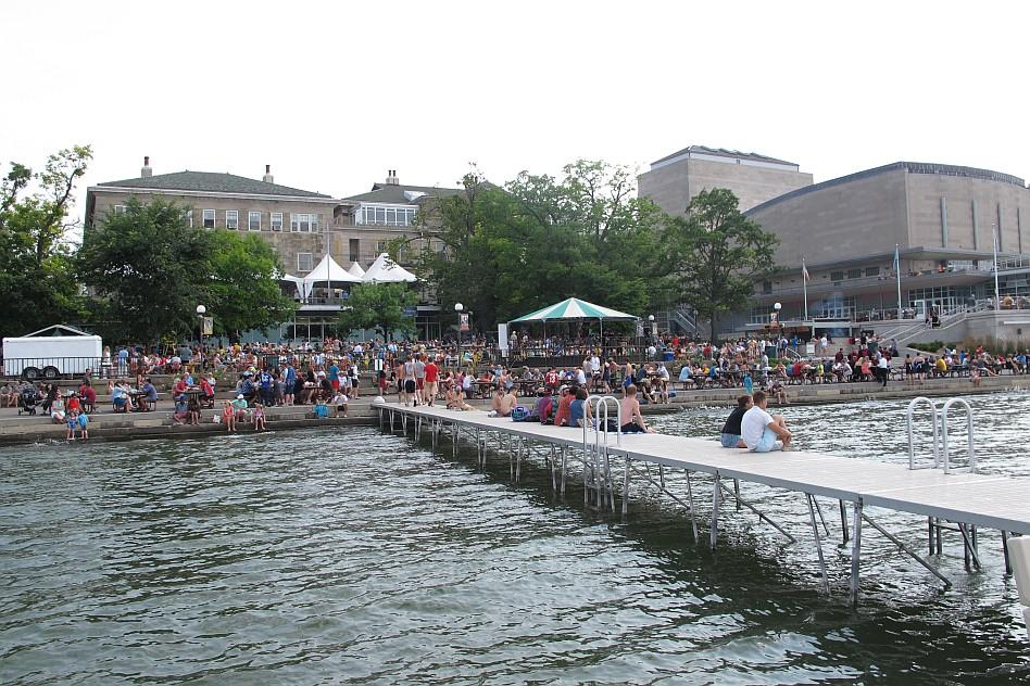 People sitting on a pier on a lake in front of campus buildings
