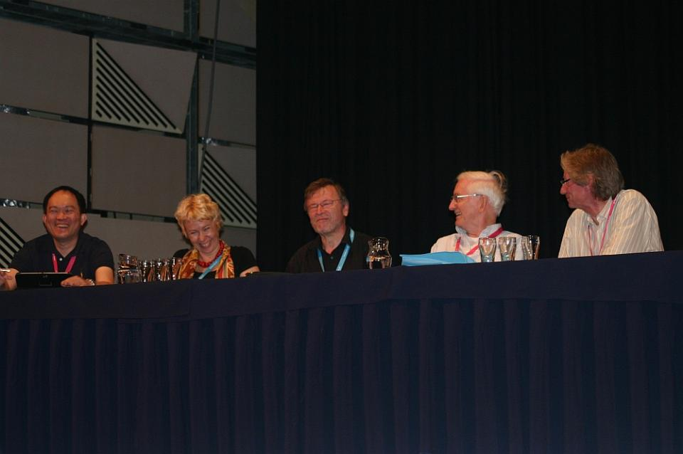 5 people sitting at a conference table with a blue tablecloth