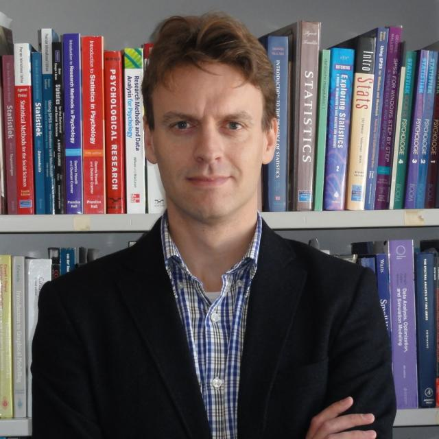 Headshot of Eric-Jan Wagenmakers in front of books