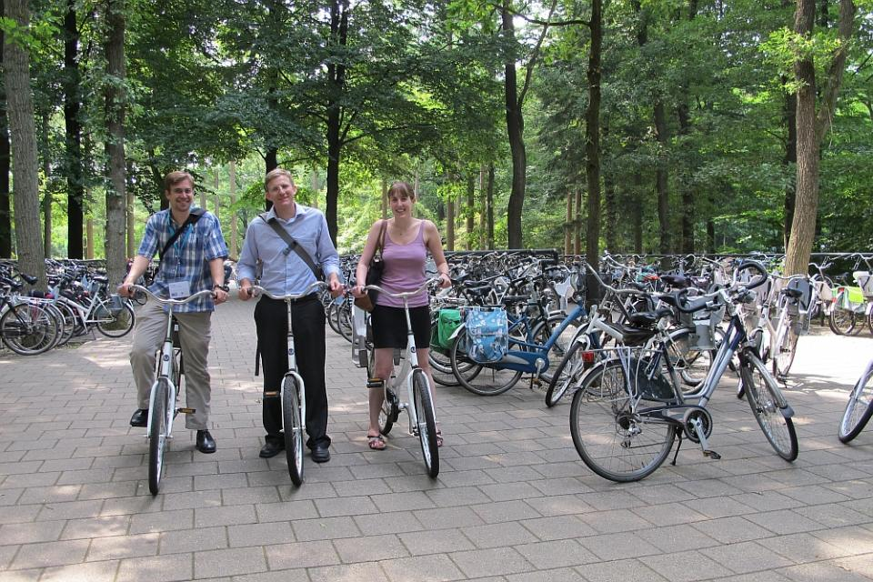 3 people riding bicycles in a park with many other parked bicycles