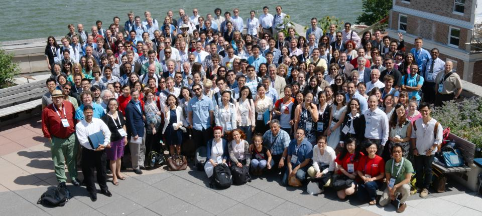 IMPS 2014 group photo, about 100 people standing in front of a lake on a sunny day