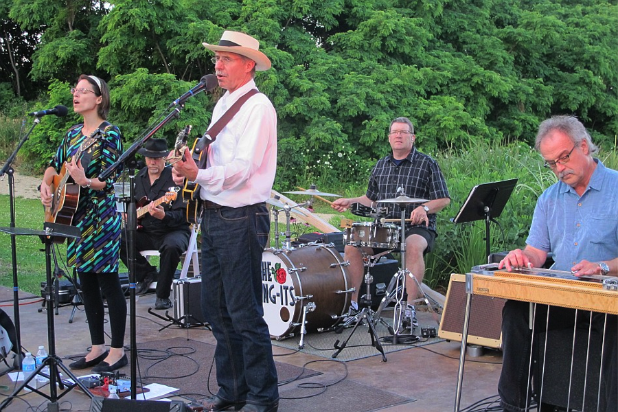 Live 4 member band playing on a stage with forest in background